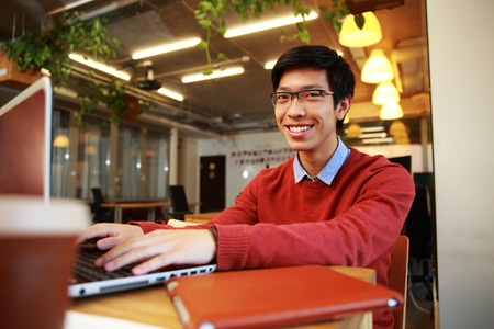 Happy asian man in glasses working on laptop in office