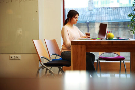 Young beautiful girl working at laptop in office photo