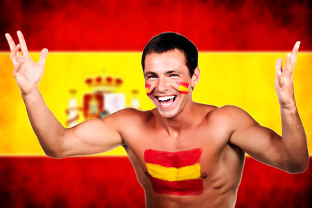 Portrait of a spanish soccer fan over spain flag background photo