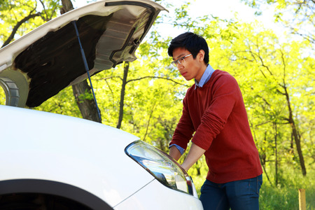 Side view portrait of a young asian man checking his car engine Stock Photo