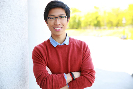 Portrait of happy asian man with arms folded photo