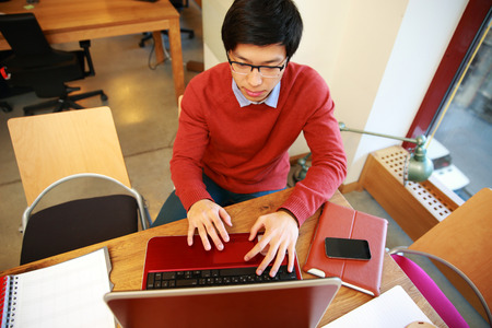 Young asian man in glasses working on laptop in office photo