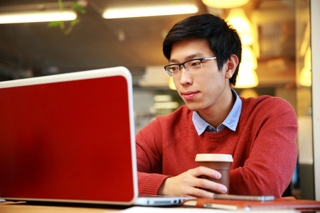 asian businessman: Young asian man in glasses working on laptop and holding cup of coffee