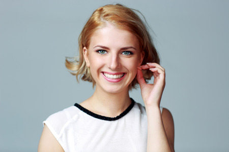 Portrait of a young happy woman touching her ear on gray background photo