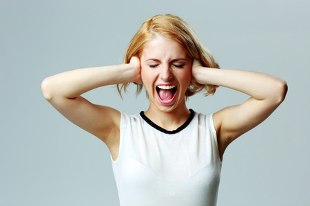 Screaming young woman with closed ears on gray background