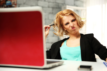 Young funny woman sitting at her workplace in office Stock Photo - 28581697