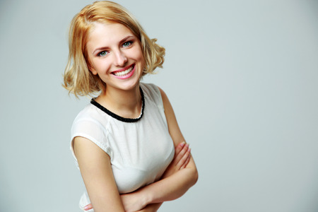 Portrait of a happy smiling woman with arms folded on gray background Stock Photo