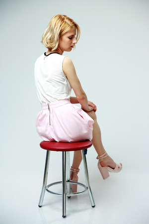 Young pensive woman sitting on the chair over gray background photo