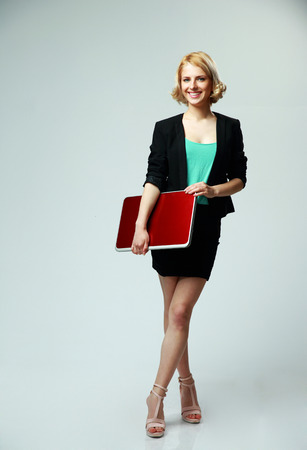 Full length portrait of a happy woman standing with laptop on gray background photo