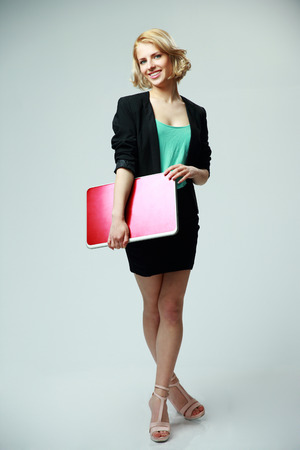 Full length portrait of a young woman standing with laptop on gray background photo