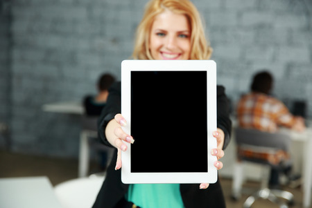 Young smiling woman showing blank tablet computer screen in office. Focus on tablet computer photo
