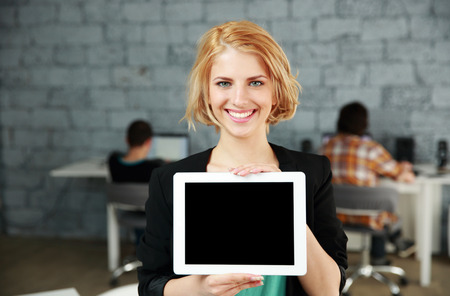 blank screen: Young happy woman showing blank tablet computer screen in office Stock Photo
