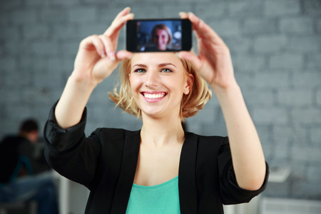 Young happy woman making a self photo by her smartphone in office photo