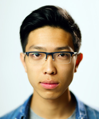 Closeup portrait of a young serious asian man on gray background photo