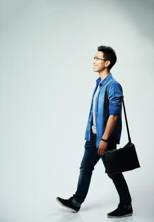 灰色の背景の上を歩く若いアジア人のスタジオ撮影