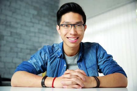asian business people: Young happy asian man sitting at the table