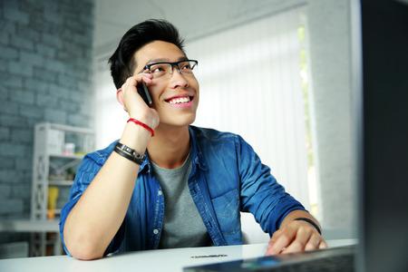 オフィスの彼の職場に電話で話している若い幸せなアジアの男