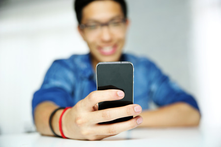 Closeup portrait of a man using smartphone. Focus on smartphone. photo