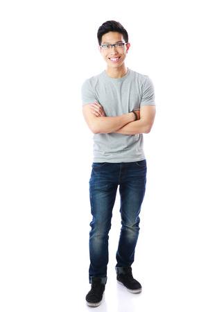 whole body: Full-length portrait of a smiling asian man with arms folded over white background