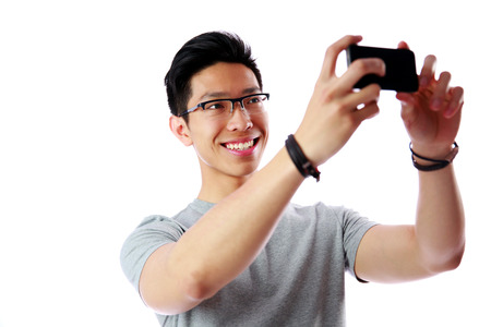 Smiling asian man taking photo with smartphone over white background photo