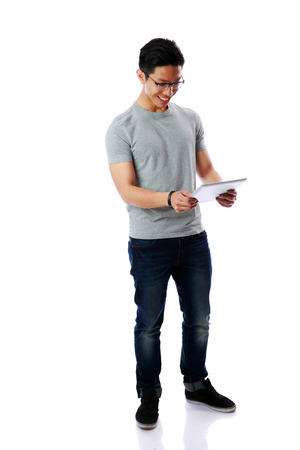 Full-length portrait of a young happy asian man standing with tablet computer over white background photo