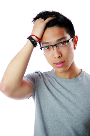 Portrait of a young serious asian man over white background photo