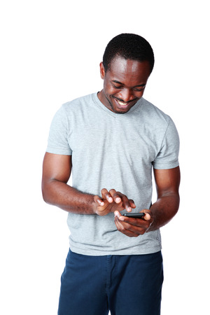 Portrait of a smiling african man using smartphone over white background photo