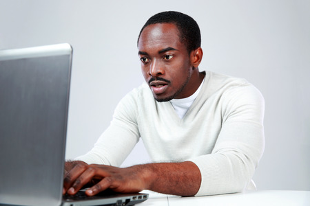 Concetrated african man using laptop on gray background photo