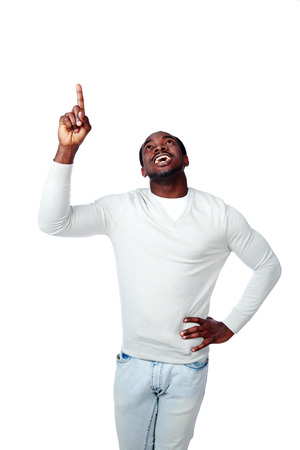 Laughing african man pointing up on white background photo