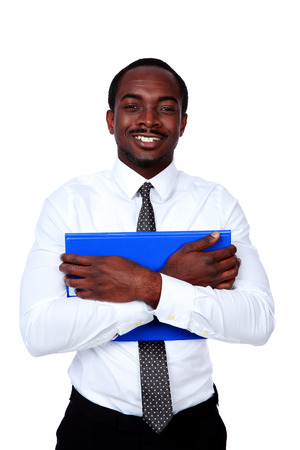 SMiling african man standing with blue folder isolated on white background photo