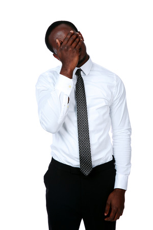Tired african businessman closed his face by his hand on white background photo
