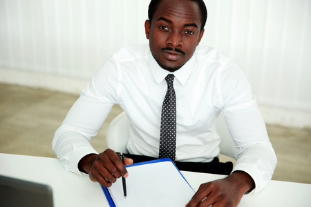 Pensive african man sitting at the table and signing document in office photo