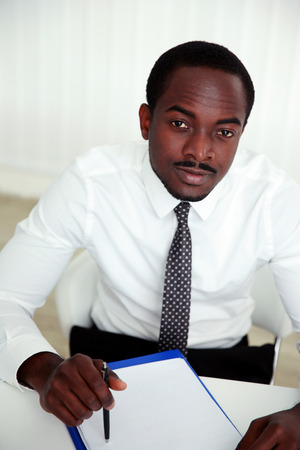 Thoughtful african man sitting at the table and signing document in office photo