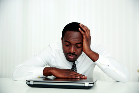 African man sleeping at his workplace in office photo