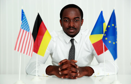 rumania: Serious african man sitting at the table in office Stock Photo