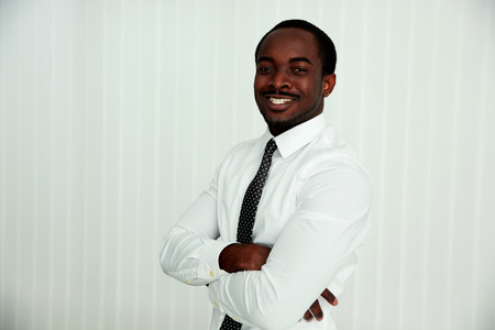 Happy african businessman with arms folded in office photo