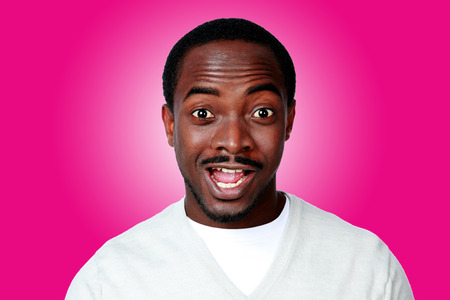 Portrait of surprised african man over pink background photo