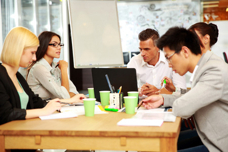 concetrated: Business people having meeting around table in office