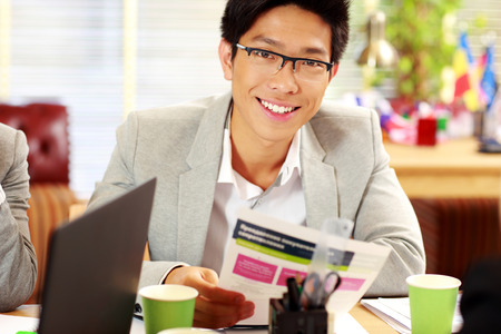Happy asian businessman in glasses sitting at the table and holding document in office photo
