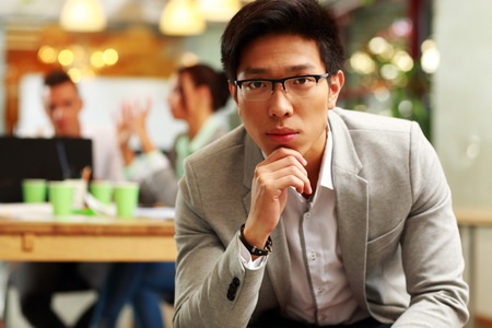Portrait of a pensive asian man sitting in office, with his colleagues in background photo
