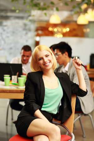Cheerful businesswoman sitting in office, with her colleagues in background photo
