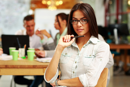 Portrait of a young beautiful businesswoman in office, with her colleagues in background photo