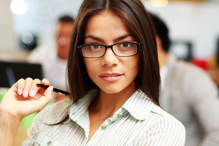 Portrait of a young thoughtful businesswoman in office, with her colleagues in background photo