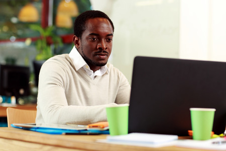 concetrated: African american businessman working on his laptop in office