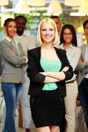 Smiling young businesswoman standing in front of colleagues at office photo