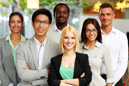 Happy group of co-workers standing in office Stock Photo