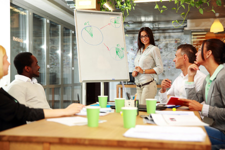busy office: Young smiling businesswoman explaining graph to his colleagues Stock Photo