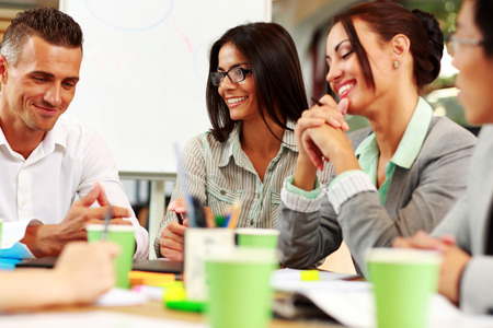 menschen sitzend: Happy Business-Leute sitzen um den Tisch in der Sitzung