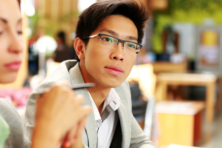Portrait of a thoughtful asian man in glasses at office photo