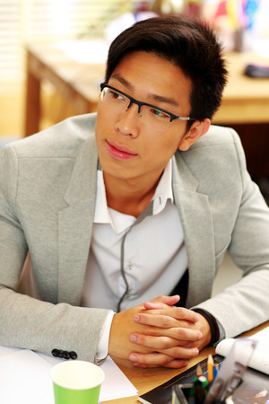 Portrait of a handsome asian man in glasses at office photo